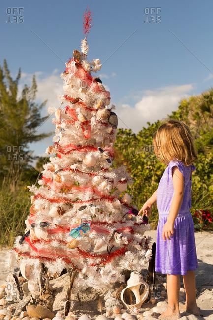 Little girl decorating Christmas tree on a beach