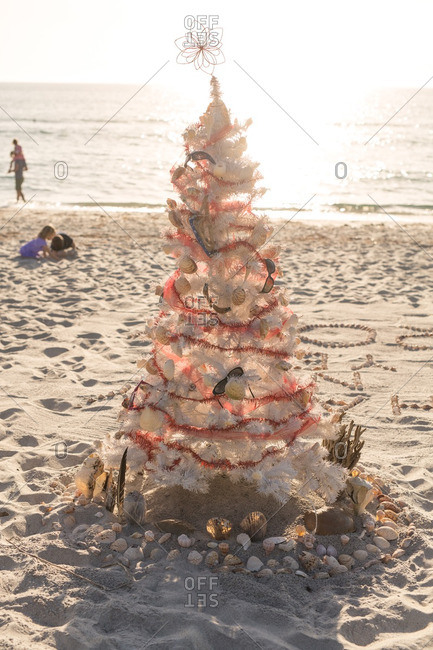 Decorated Christmas tree on a beach with children playing in the background