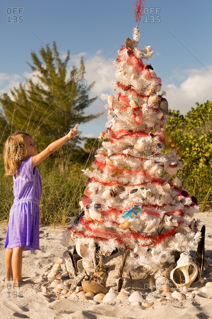 Little girl pointing to a decorating Christmas tree on a beach