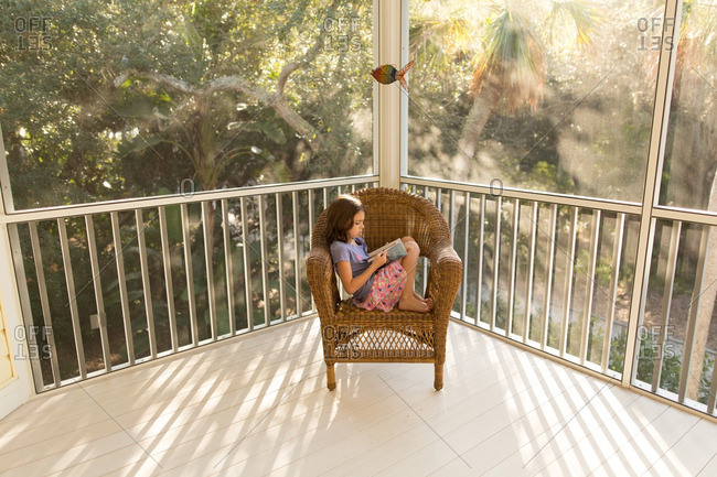 Little girl reading a book on a whicker chair on a porch