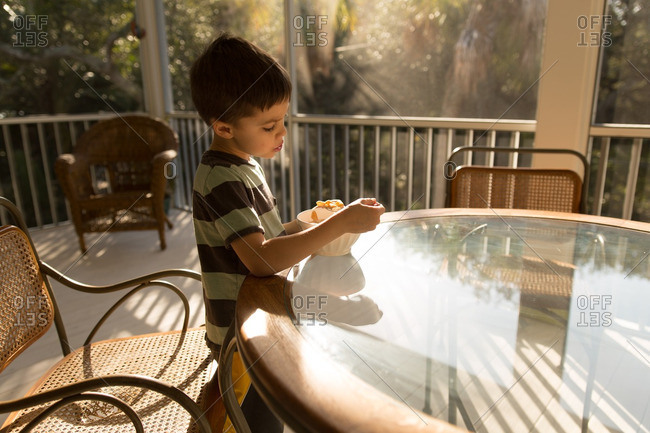 Little boy eating a bowl of cereal on a table outdoors
