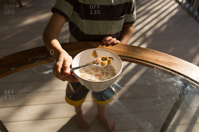 Overhead view of a boy eating a bowl of cereal on a table outdoors