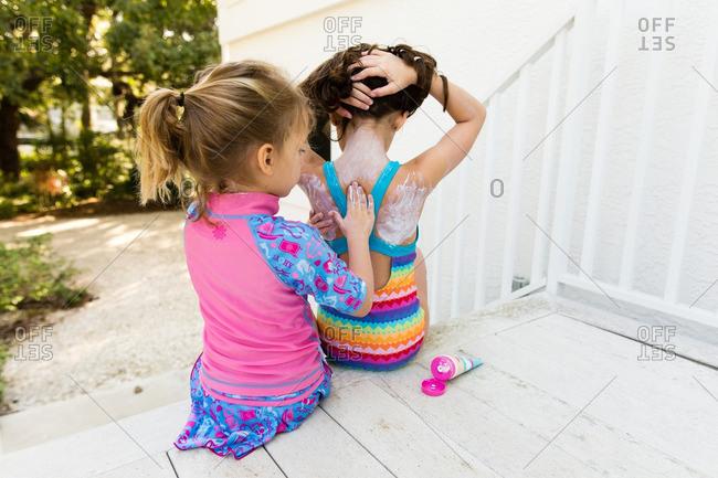 Little girl rubbing sunscreen onto her sister's back