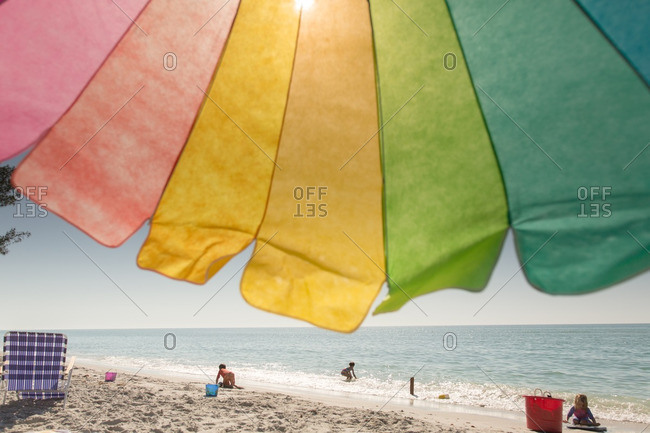 Colorful umbrella on a beach with kids playing in the distance