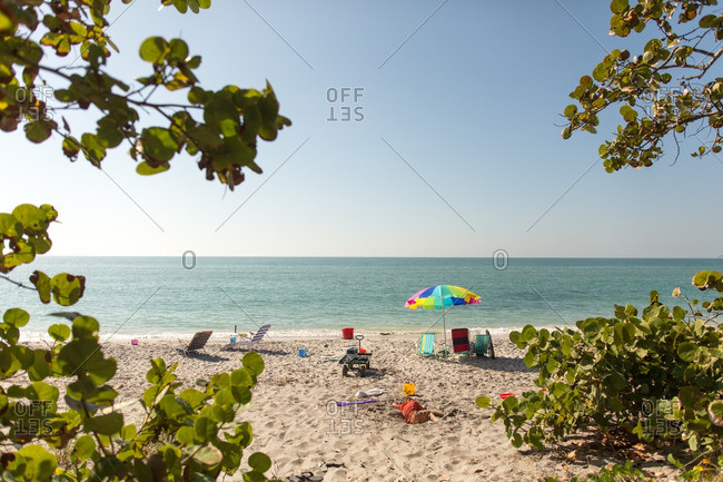 View of ocean and beach with lounge chairs and an umbrella