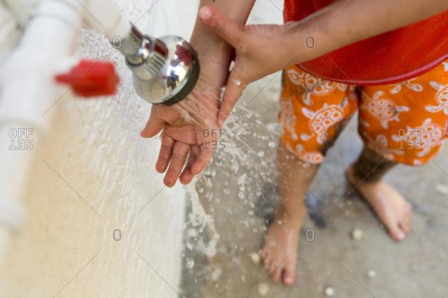 Boy rinsing his hand under water