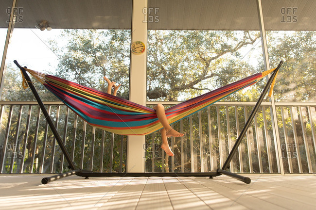 Boy lying in a colorful hammock with his hands in the air