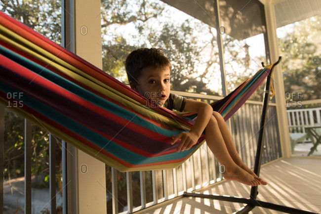 Boy in a colorful hammock on a screened in porch