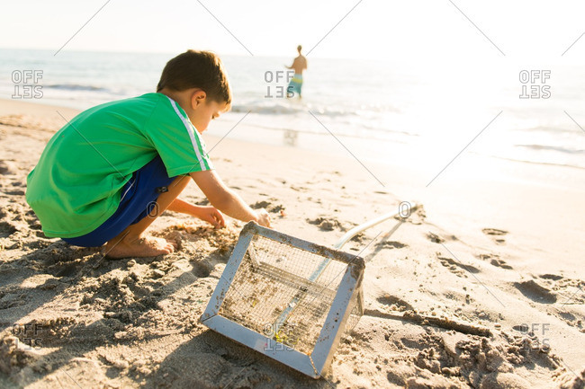Boy digging in the sand on a beach