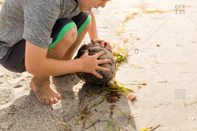 Boy finding a coconut on a beach