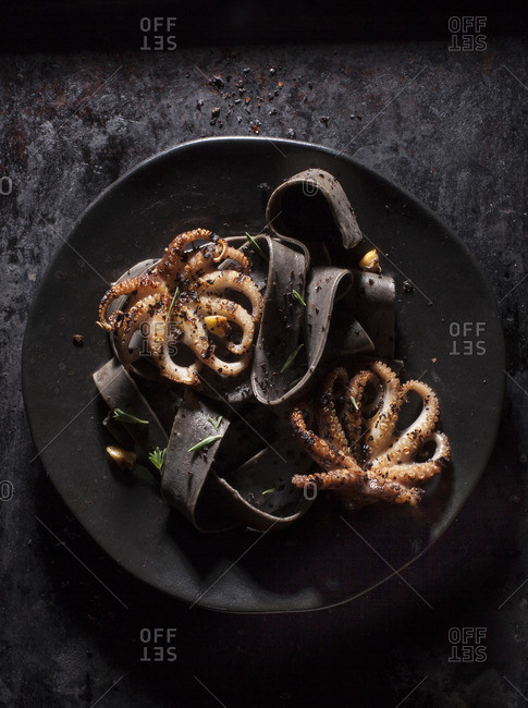 Black plate with two grilled octopus and black noodles on dark background