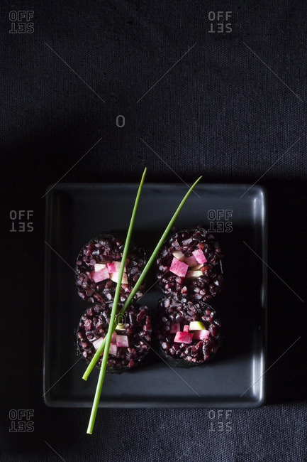 Square plate vegetarian sushi rolls with black rice