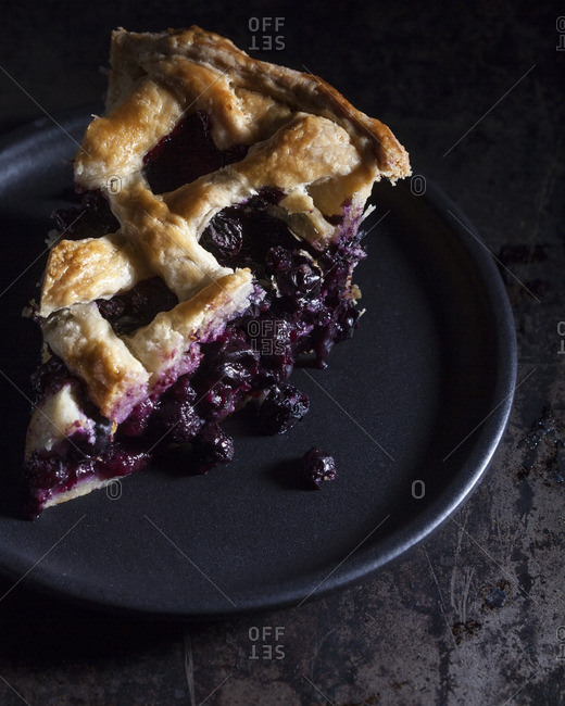 blueberry pie on black plate with lattice crust