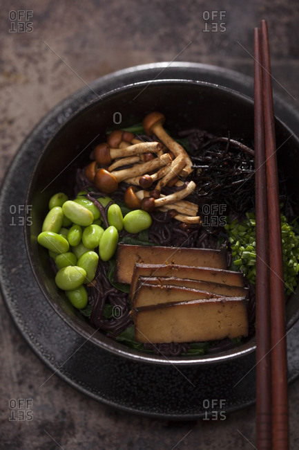Black ramen noodles with sliced tofu, edamame, mushrooms, and chives