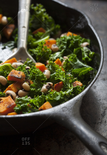 Cast iron skillet of kale, sweet potatoes, and black eyed peas