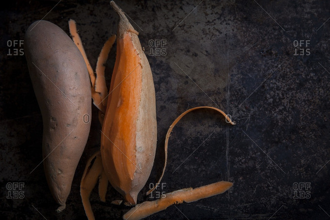 Peeling sweet potatoes on dark background
