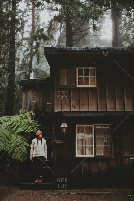 Woman standing on porch of rainforest cottage