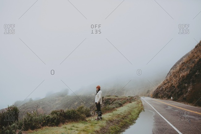 Woman overlooking foggy valley from edge of road