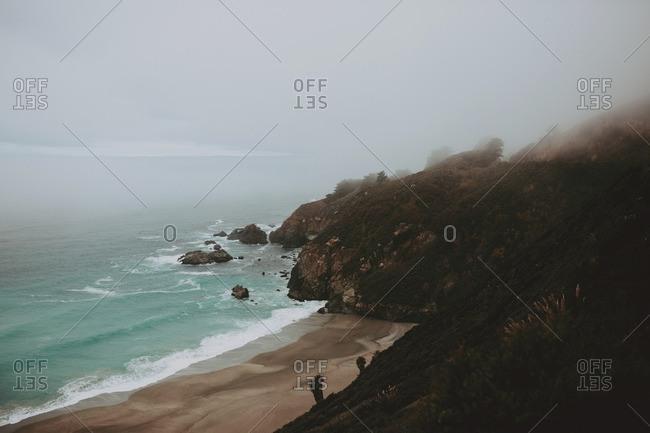 Sand beach below a cliff in foggy weather