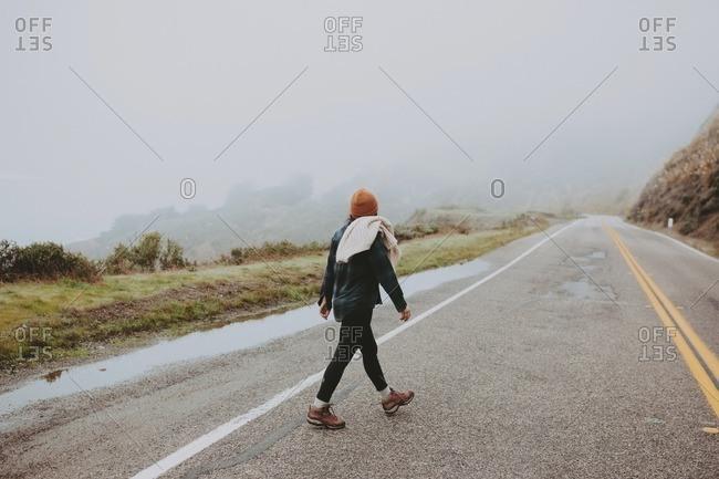 Woman walking on road in foggy weather