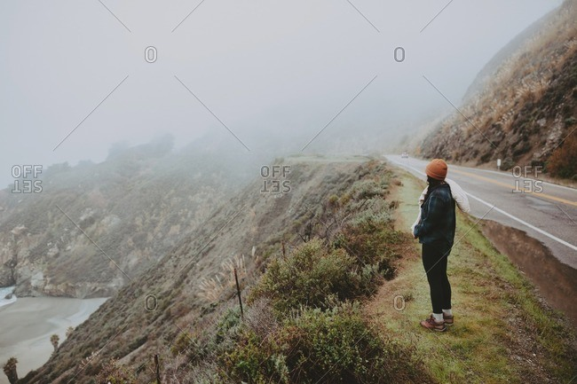 Woman overlooking foggy beach from edge of road