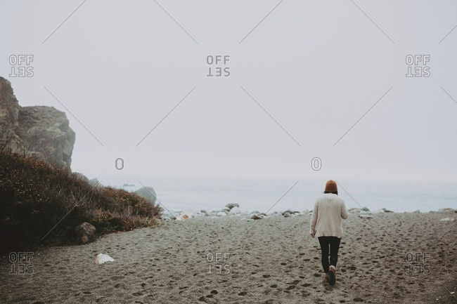 Woman walking toward ocean on foggy beach