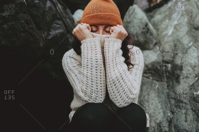 Close-up of woman covering her face with her sweater
