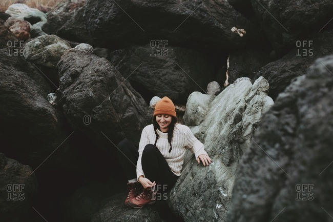 Smiling woman with braids resting on rocks on the seashore