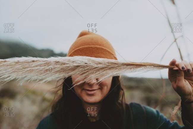 Woman holding feathery stalk of beach grass in front of her eyes