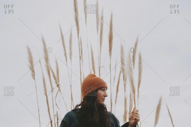 Woman amidst feathery tall beach grass