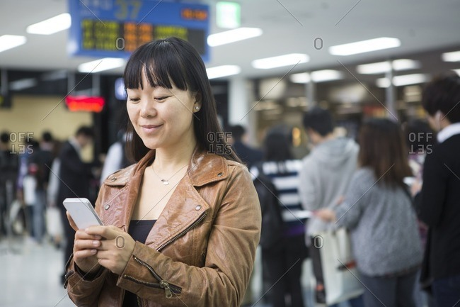 Asian woman using a cell phone at the airport
