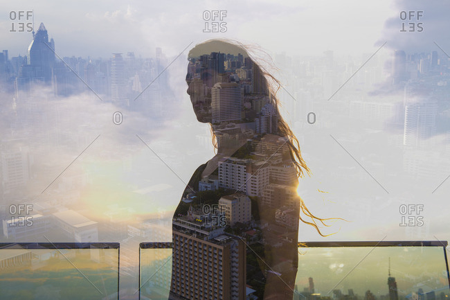 Double exposure of woman overlooking a cityscape