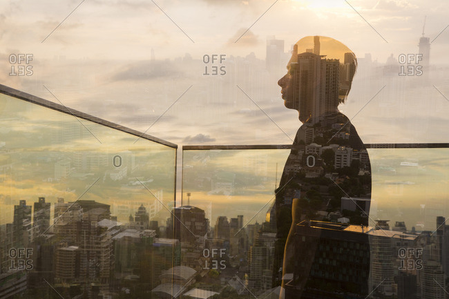 Double exposure of young man looking out over cityscape