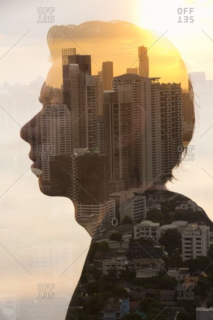Silhouette of young man superimposed over cityscape