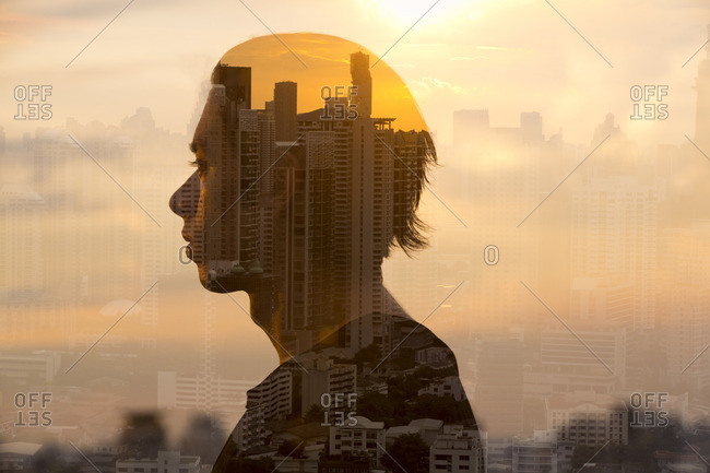 Double exposure image of man looking out at a cityscape