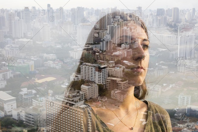 Double exposure of portrait of young woman over a city scene