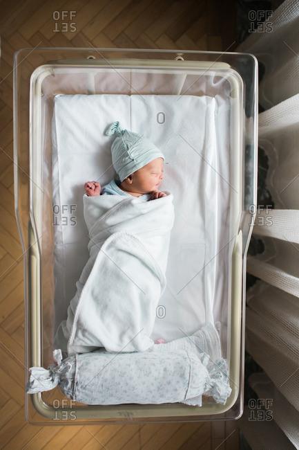 Overhead view of baby sleeping in hospital bassinet