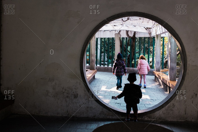 Three young children explore a Chinese garden