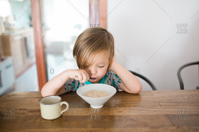 Young boy eats breakfast at dining table