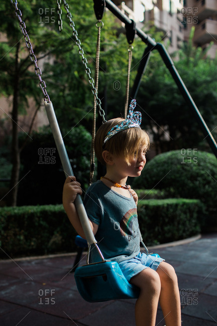 Child in tiara on playground swings