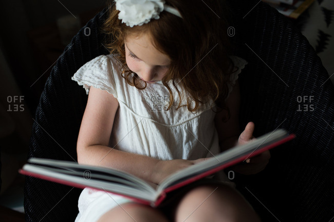 Girl in white dress reads a book
