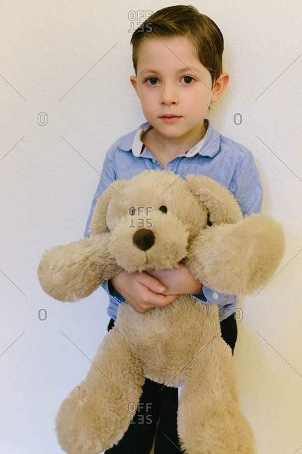 Young boy holding a brown stuffed dog