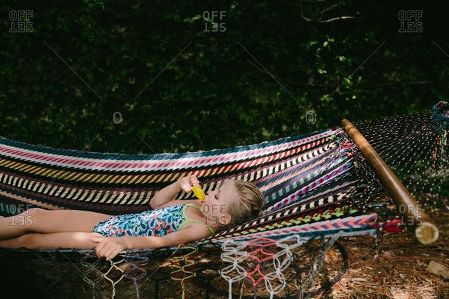 Girl eating ice pop while lying on hammock
