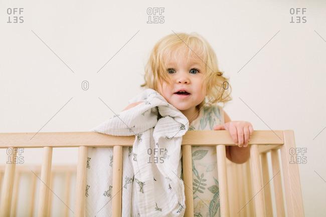 Baby girl peeking over side of crib