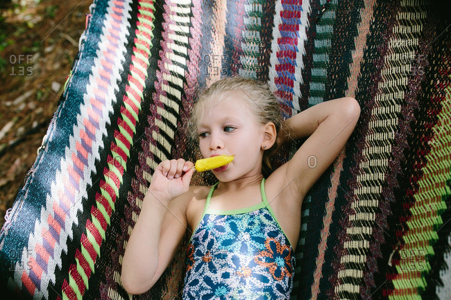 Young girl eating an ice pop while lying on a hammock