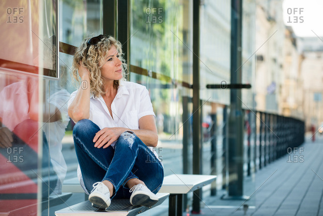 Contemplative mature woman sitting on bus bench, looking away