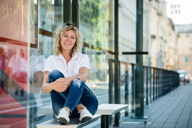 Lady relaxing on bus bench with a toothy smile
