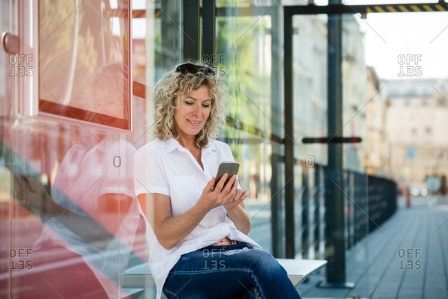 Lady sitting at bus stop with a phone, messaging friends
