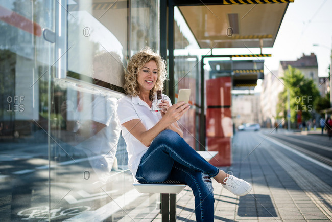 Mature woman messaging from her phone at bus stop while eating chocolate