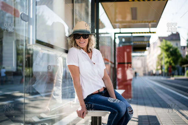 Mature woman waiting at bus stop, wearing sun glasses, and hat